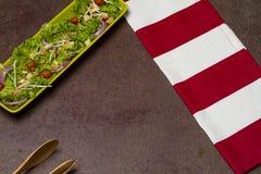 Świeża sałatka pomidorowa sałata i cebula z czerwienią paskował płótno, chleb koronki i drewnianą łyżkę, obrazy stock