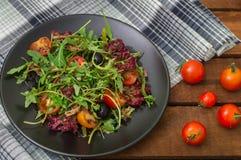 Świeża sałatka z arugula, garnelą, czereśniowym pomidorem i avocado, Drewniany tło Zakończenie Odgórny widok Zdjęcie Royalty Free