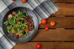 Świeża sałatka z arugula, garnelą, czereśniowym pomidorem i avocado, Drewniany tło Zakończenie Odgórny widok Fotografia Stock