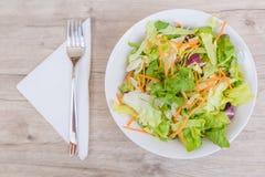Świeża sałatka z czereśniowymi pomidorami, szpinakiem, arugula, romaine i sałatą w talerzu na białym drewnianym tle, odgórny wido fotografia stock