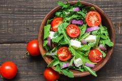 Świeża sałatka z rucola, pomidorami wiśnia, feta serem i czerwoną cebulą w pucharze na nieociosanym drewnianym stole, Odgórny wid zdjęcia royalty free