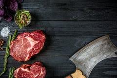 Świeża surowa wołowina z basilem i sprig rozmaryny z ax dla mięsa na czarnym drewnianym tle Odgórny widok Fotografia Royalty Free