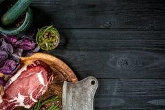 Świeża surowa wołowina z basilem i sprig rozmaryny z ax dla mięsa na czarnym drewnianym tle Odgórny widok Zdjęcie Royalty Free