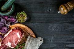 Świeża surowa wołowina z basilem i sprig rozmaryny z ax dla mięsa na czarnym drewnianym tle Odgórny widok Obraz Stock