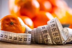 Świeża tropikalna owoc i miara taśmy Tangerines, obrany tangerine i tangerine plasterki na błękitnym płótnie, Mandarine sok Obrazy Royalty Free