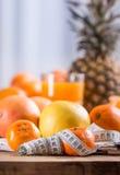 Świeża tropikalna owoc i miara taśmy Tangerines, obrany tangerine i tangerine plasterki na błękitnym płótnie, Mandarine sok Zdjęcia Royalty Free
