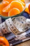 Świeża tropikalna owoc i miara taśmy Tangerines, obrany tangerine i tangerine plasterki na błękitnym płótnie, Mandarine sok Obrazy Stock
