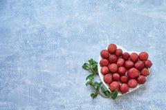 Świeża truskawka z mennicą w kierowym kształcie na betonowym tle Zdjęcia Royalty Free