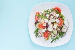 Świeża wiosny sałatka z ogórkiem, pomidorem, serem i arugula odizolowywającymi na białym talerzu, obraz royalty free