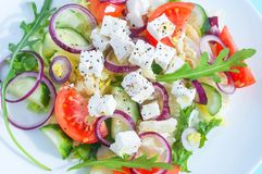 Świeża wiosny sałatka z ogórkiem, pomidorem, serem i arugula odizolowywającymi na białym talerzu, obraz stock