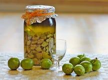 Świeża zieleń, młodzi orzechy włoscy i butelka domowej roboty ajerkoniak brać jako remedium dla żołądek obolałość, obrazy stock