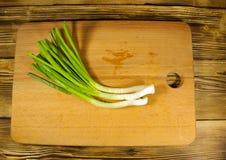 Świeża zielona cebula na tnącej desce na drewnianym stole Zdjęcia Stock