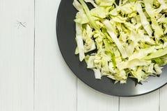 Świeża zielona kapusta na czarnym talerzu na białym stole Przestrzeń dla teksta zdjęcia stock