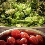 Świeża zielona sałatka i opłukujący czereśniowi pomidory w pucharach na kitc zdjęcie royalty free