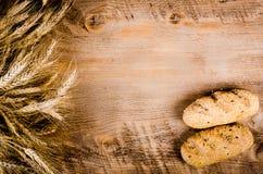 Świeże babeczki i pszeniczni ucho na drewnianym tle Rama Zdjęcie Stock