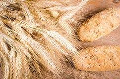 Świeże babeczki i pszeniczni ucho w czarnym tle Zdjęcia Stock
