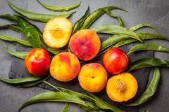 Świeże brzoskwinie na czerń kamienia talerzu, szarości łupkowy tło Zdjęcie Stock