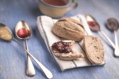 Świeże chlebowe rolki kłama na kuchennym ręczniku z dżemem w łyżkach i filiżance herbata wokoło go obok go Zdjęcie Stock