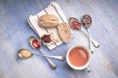 Świeże chlebowe rolki kłama na kuchennym ręczniku z dżemem w łyżkach i filiżance herbata wokoło go obok go Obrazy Stock