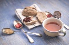 Świeże chlebowe rolki kłama na kuchennym ręczniku z dżemem w łyżkach i filiżance herbata wokoło go obok go Obrazy Royalty Free