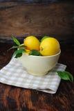 Świeże cytryny w pucharze na stole Obrazy Royalty Free