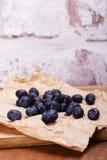 Świeże czarne jagody na nieociosanym brown papieru tle obrazy royalty free