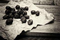 Świeże czarne jagody na nieociosanym brown papieru tle obrazy stock