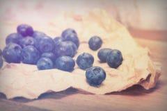 Świeże czarne jagody na nieociosanym brown papieru tle obraz stock