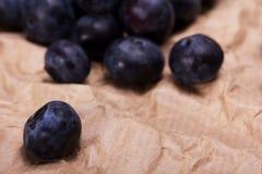 Świeże czarne jagody na nieociosanym brown papieru tle obraz royalty free