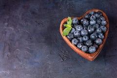 Świeże czarne jagody z liściem mennica w sercowatym pucharze na zmroku - błękitny tło Obrazy Royalty Free