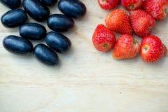 Świeże czerwone truskawki i winogrona na drewnianym tle Zdjęcia Royalty Free