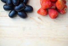 Świeże czerwone truskawki i winogrona na drewnianym tle Obraz Stock