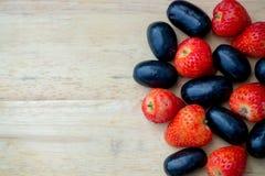 Świeże czerwone truskawki i winogrona na drewnianym tle Obraz Royalty Free
