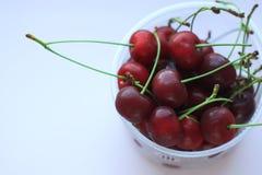 Świeże czerwone wiśnie w pucharze na menchia proszku zaświecają tło Odbitkowa przestrzeń, minimalistic styl obrazy stock