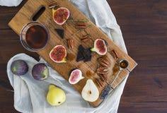 Świeże figi, bonkrety i pekan dokrętki z miodem na drewnianej desce, Zdjęcie Royalty Free