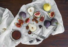 Świeże figi, czekolada, bonkrety i pekan dokrętki z miodem na drewnie, Zdjęcia Royalty Free