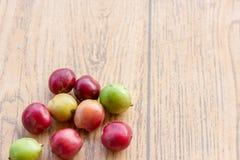 Świeże kawowe fasole na drewno stole, czerwona owoc z kofeiny addicti zdjęcia royalty free