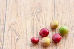 Świeże kawowe fasole na drewno stole, czerwona owoc z kofeiny addicti zdjęcia stock