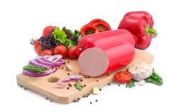 Świeże kiełbasy, sałata, czerwony pieprz i pomidory na drewnianej desce, Mięsny skład na białym tle obraz stock