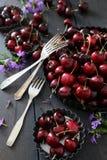 Świeże lato wiśnie, kwiaty w talerzach i Fotografia Stock