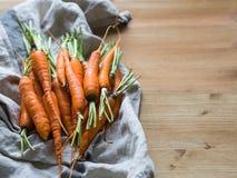 Świeże młode pomarańczowe marchewki na kuchennym ręczniku na drewnianym stole kosmos kopii zdjęcia stock