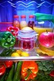 Świeże malinki w szklanym słoju na półce otwierają chłodziarkę obrazy stock