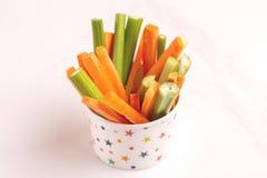 Świeże marchewki i selerowi kije w papierowej filiżance zdjęcie stock