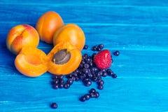 Świeże morele, truskawki i czarne jagody na drewnianym turkusowym tle, zdjęcie royalty free
