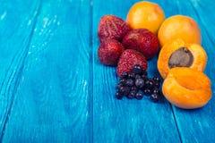 Świeże morele, truskawki i czarne jagody na drewnianym turkusowym tle, fotografia stock