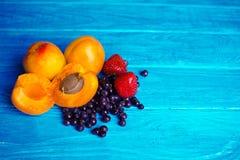 Świeże morele, truskawki i czarne jagody na drewnianym turkusowym tle, zdjęcia stock