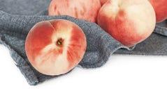 Świeże organicznie brzoskwinie na błękitnej tkaninie fotografia royalty free