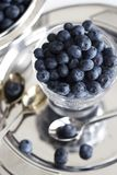 Świeże organicznie czarne jagody w przejrzystym szklanym pucharze na białym bac obraz stock