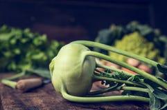 Świeże organicznie kalarepy na nieociosanym kuchennym stole z ogrodowymi warzywami Zdjęcie Stock