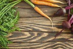 Świeże organicznie marchewki i buraki z wierzchołkami na drewnianym stole zdjęcie royalty free